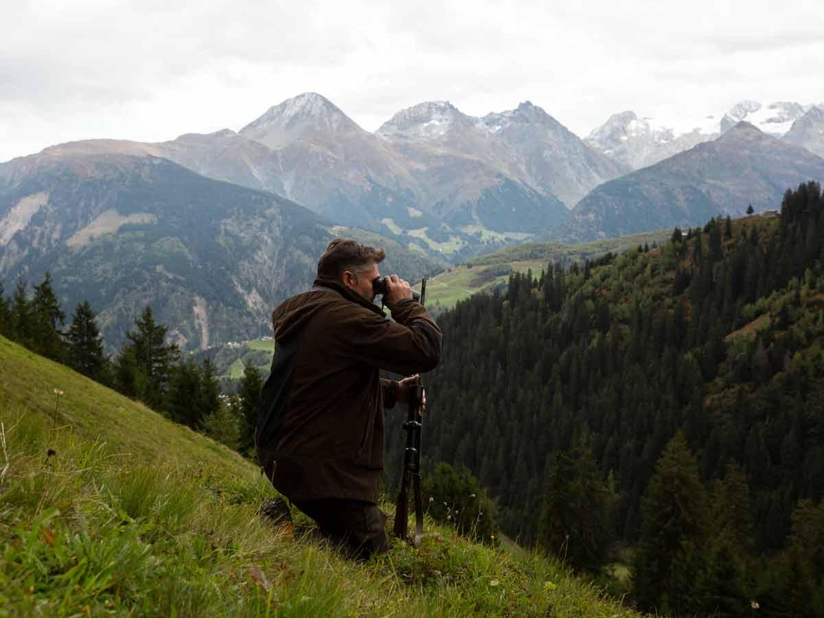 Mann-mit-Feldstecher-Ausschau-auf-Jagd-Disentis