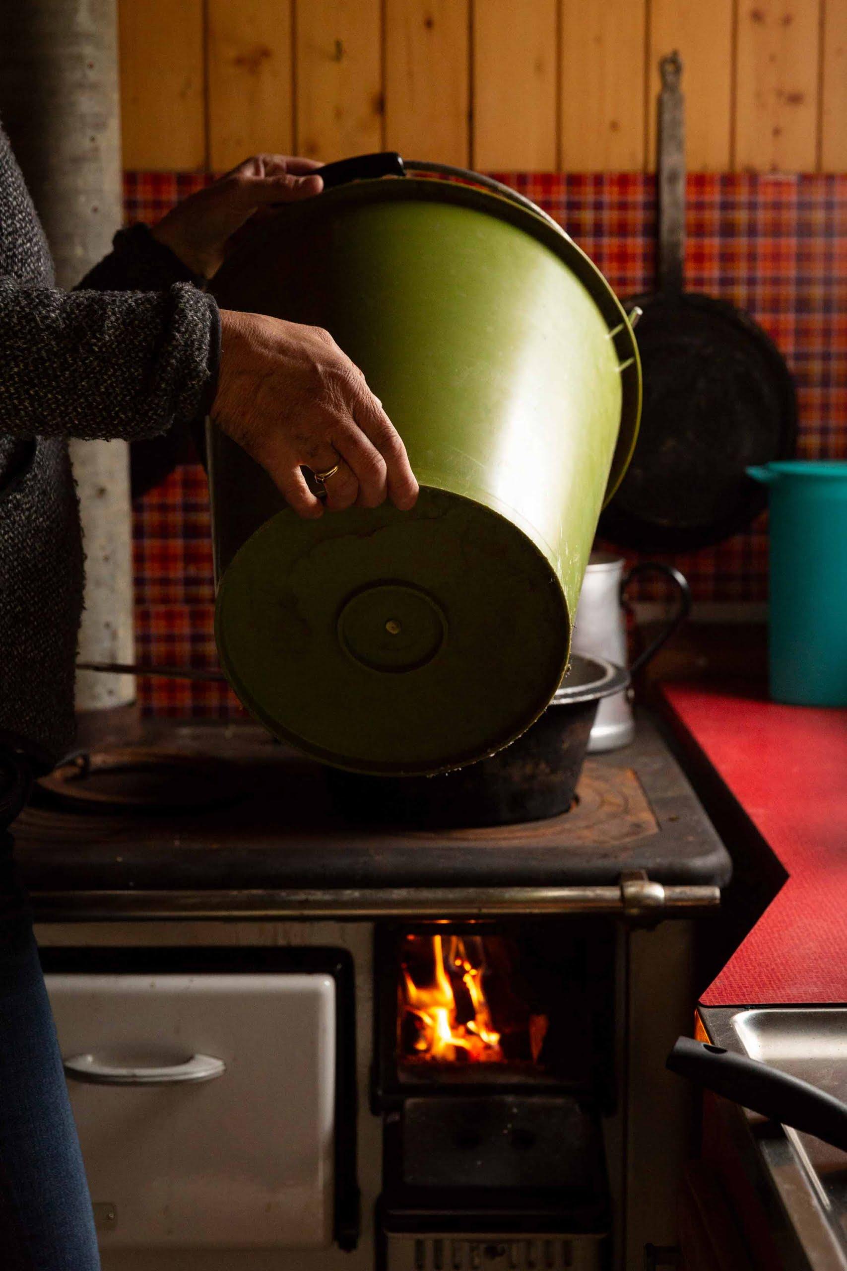 Stilleben-Alphuette-Frau-mit-gruenem-Kessel-Feuer-brennt